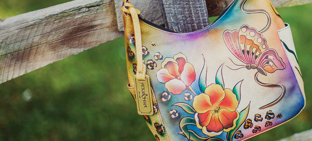 Leather handbag with illustrative nature print hanging on a wooden fence.