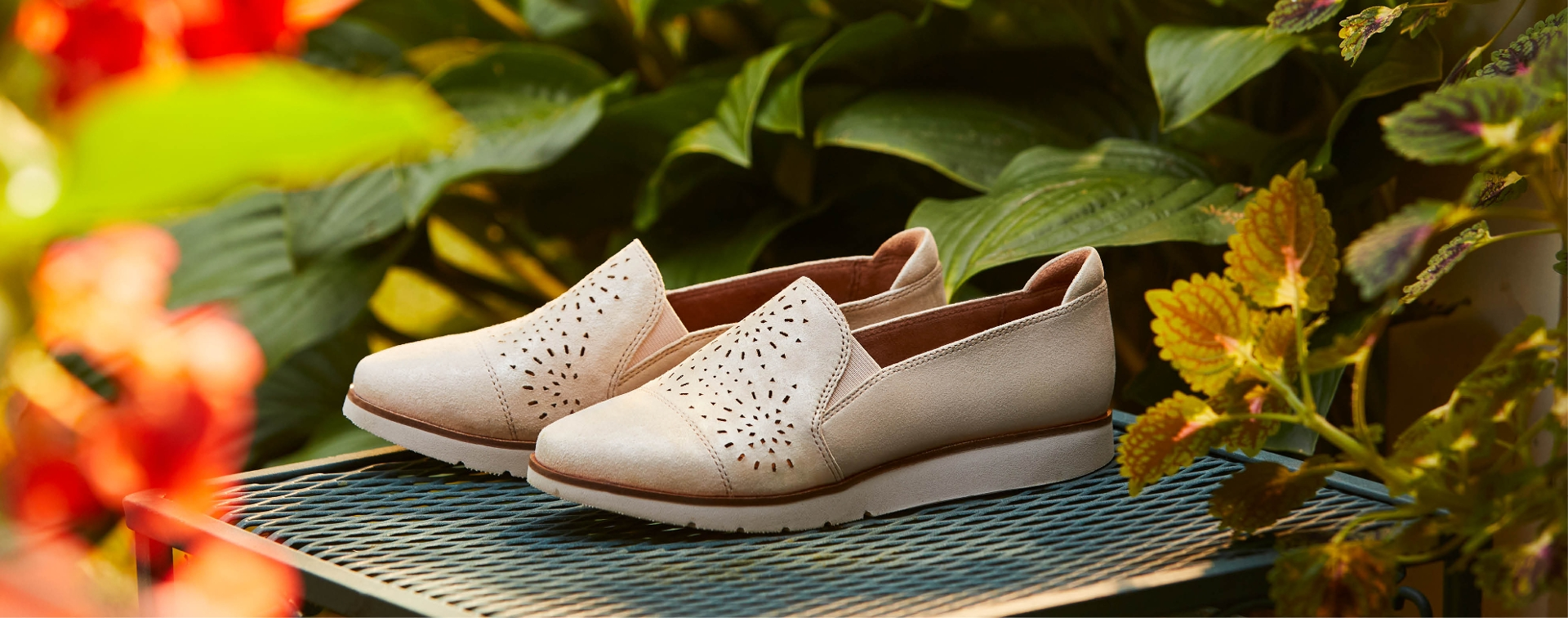Pair of women's tan shoes sitting near plants.