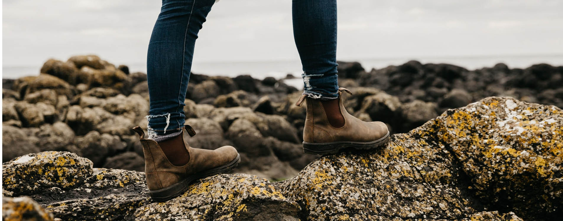Feet with Blundstone boots standing on rocks.