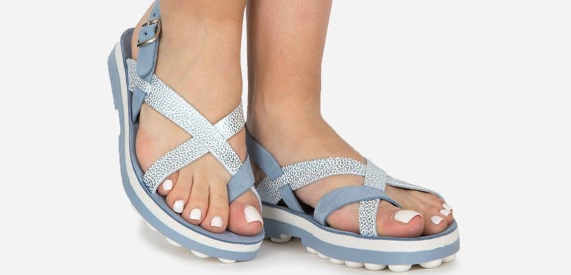 Feet with white nail polish wearing blue sandals against a white background