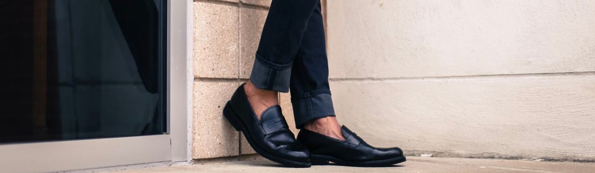 Feet in black oxfords resting against brick wall
