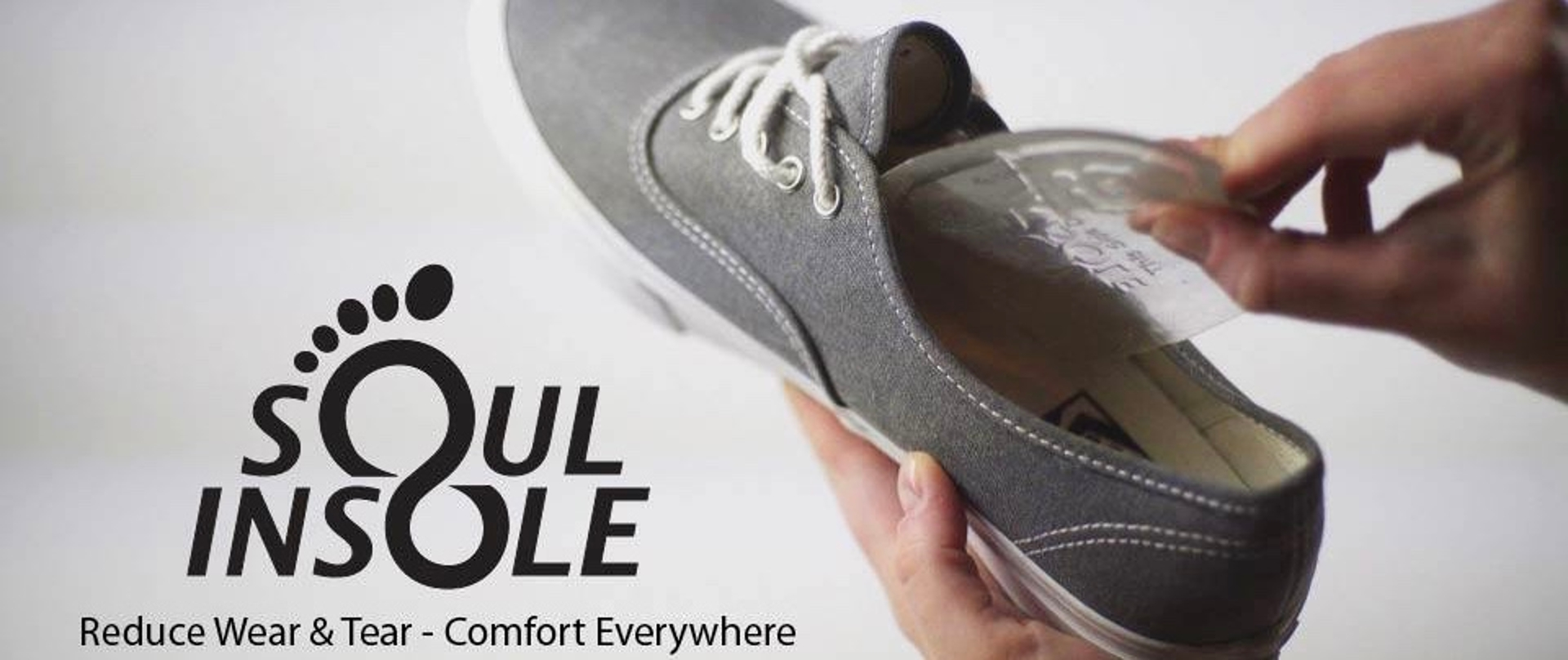 Hands inserting Soul Insole into gray shoe