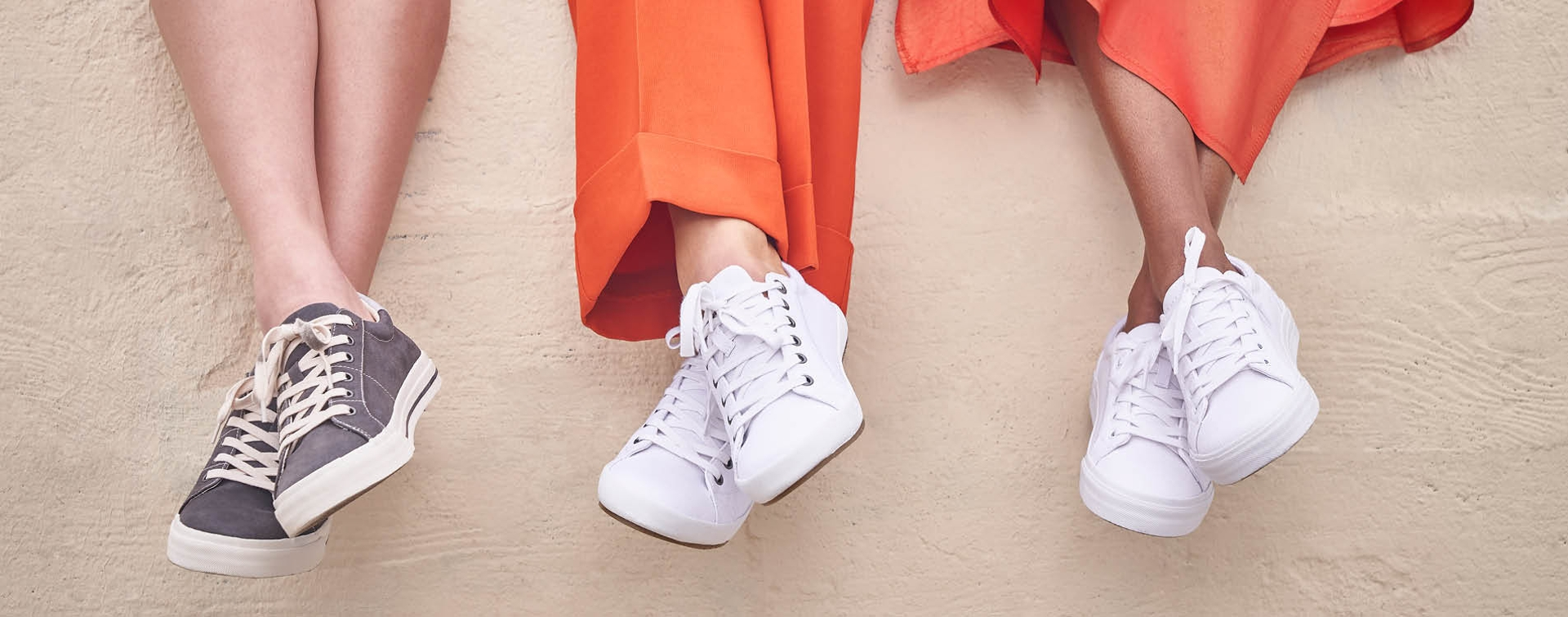 Close up shot of 3 ladies feet dangling over a brick wall wearing Taos Sneakers.