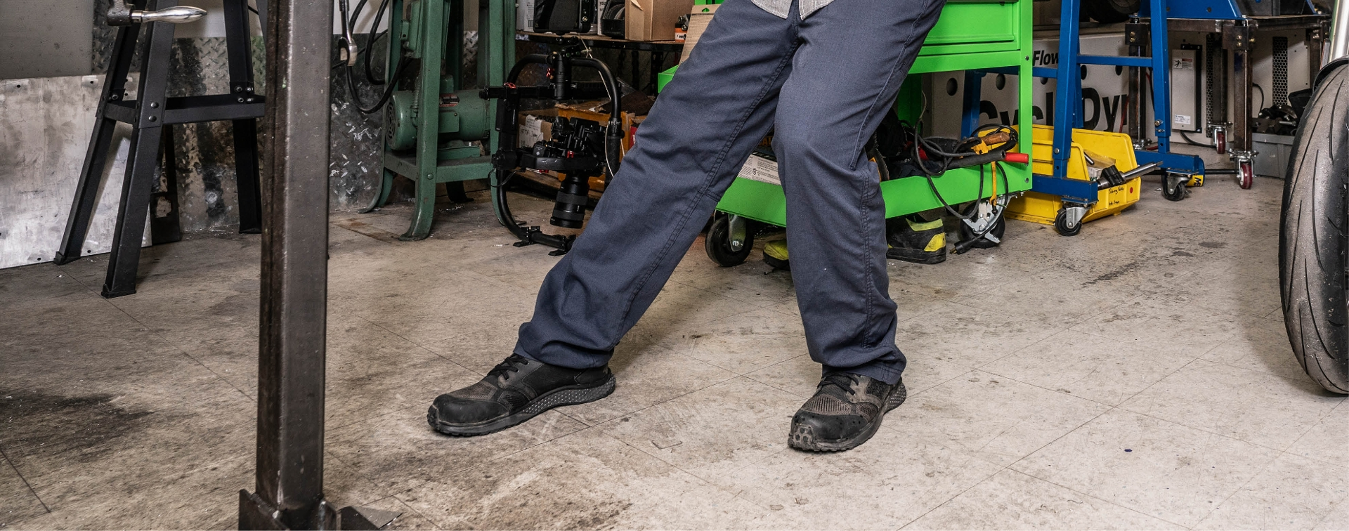 close up of guy working in a shop wearing black shoes