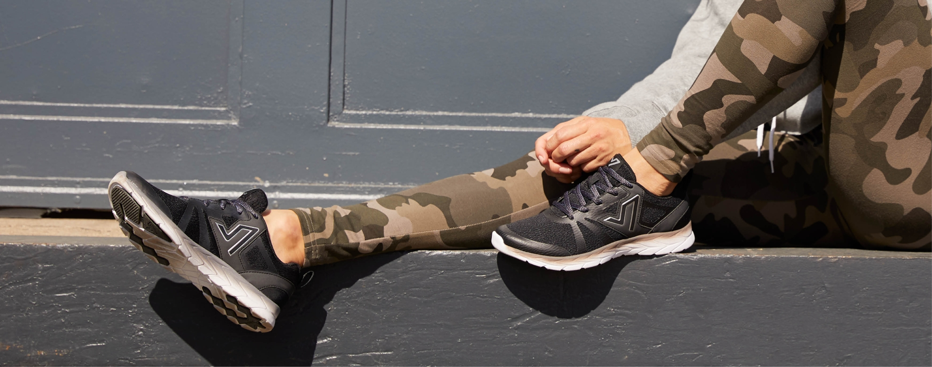 girl sitting on a wall with legs out wearing camo pants an a black pair of shoes in